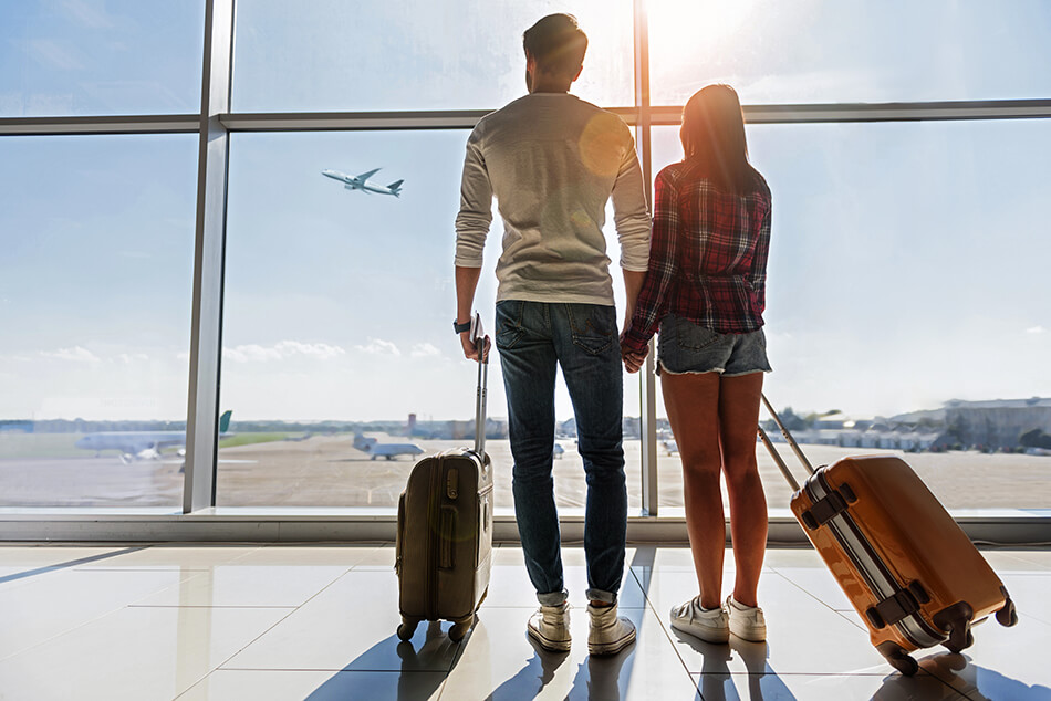 man and woman with suitcases in an airport watching a plane take off