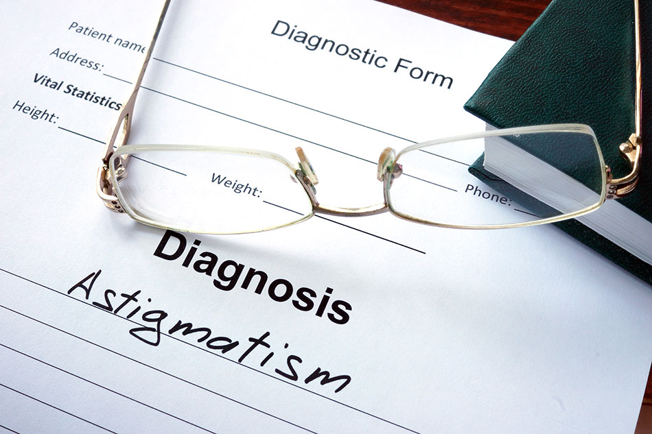 pair of glasses lying on Diagnosis form with word Astigmatism written on it