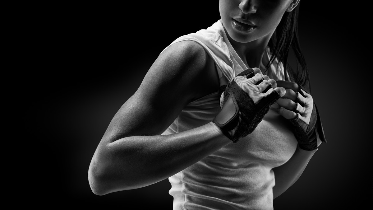 athletic woman with gloves on in grayscale