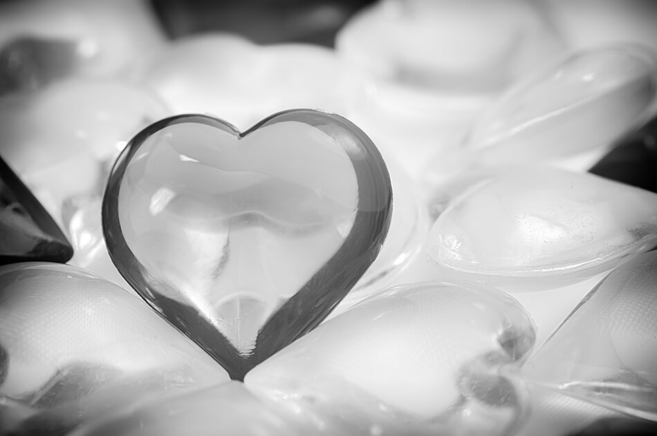 black and white photo of one small glass heart standing out among many