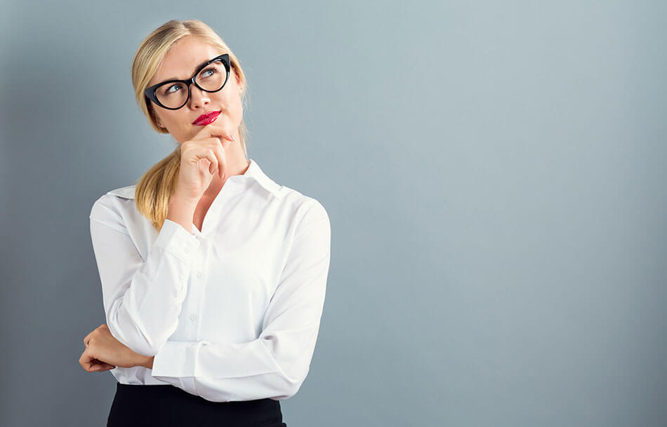 blonde woman in white blouse with black glasses on in a thoughtful pose