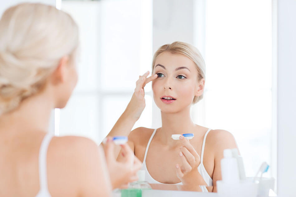 blonde woman putting contacts in mirror