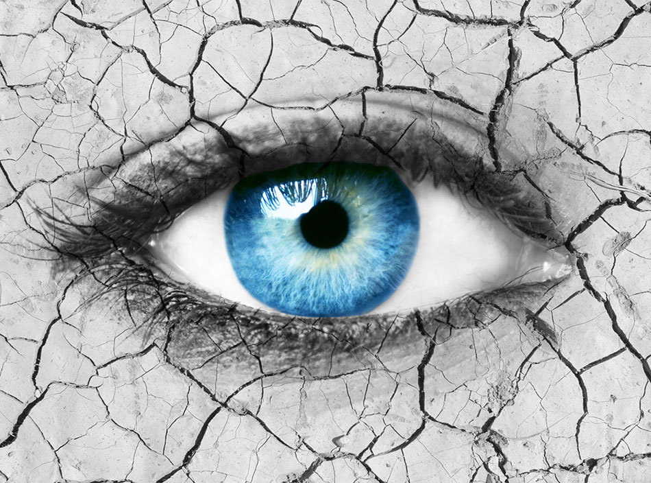 Woman's blue eye over dry cracked ground