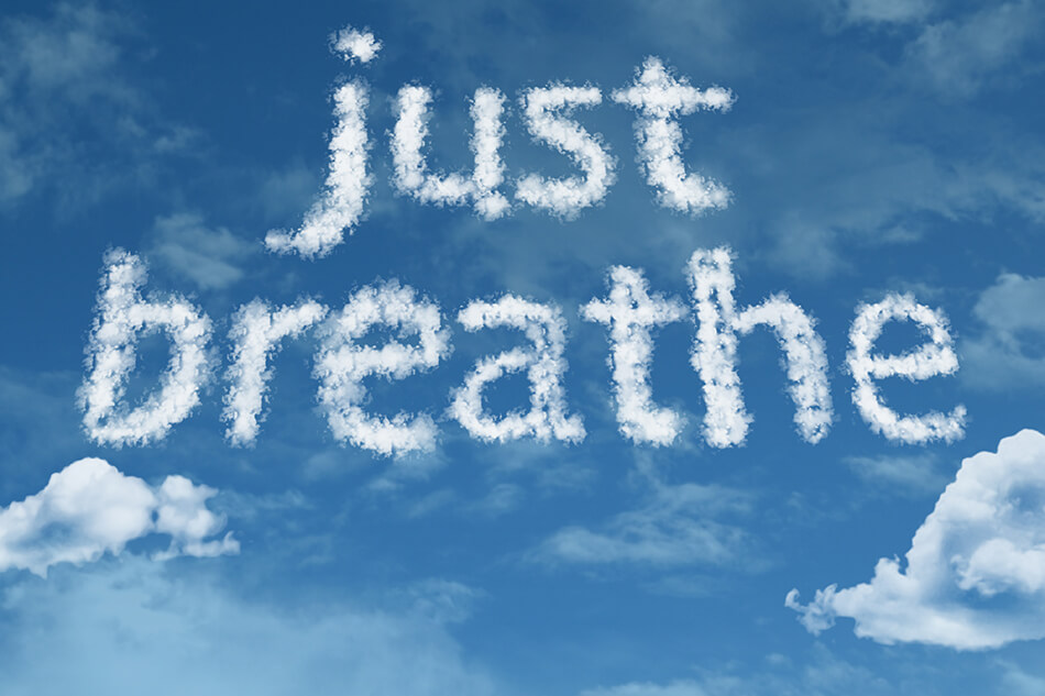 blue sky and clouds with just breathe written in white smoke