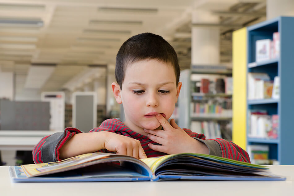 boy reading a book with one finger in his mouth and one on a page