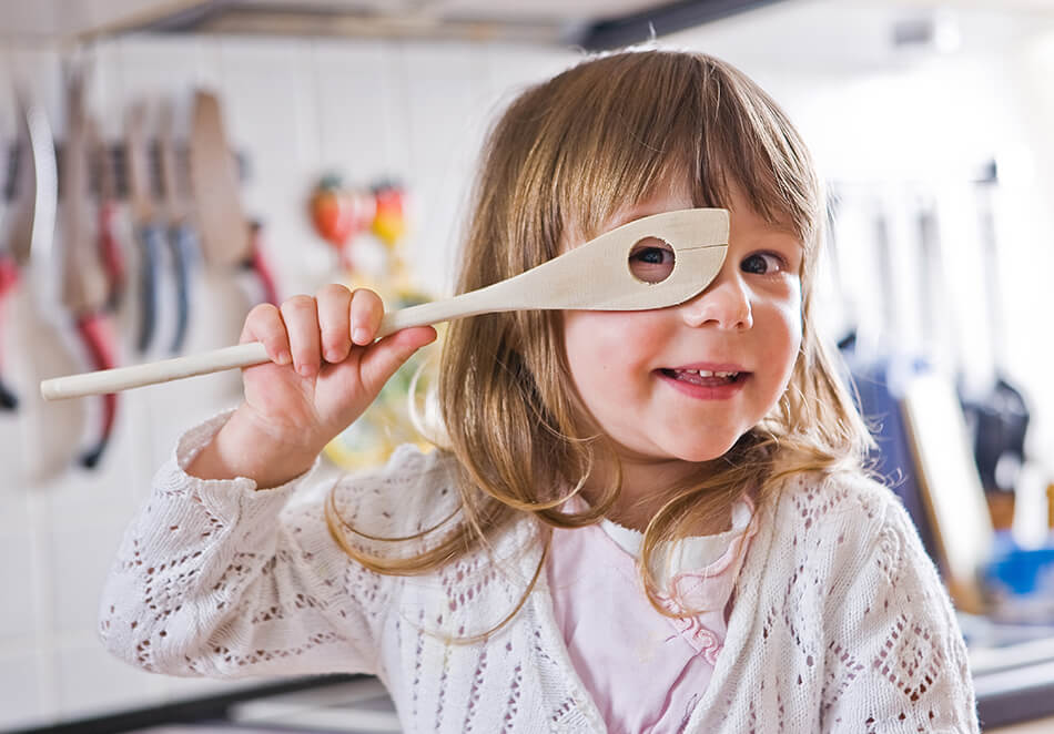 child looking through wooden spoon she's holding up to her eye
