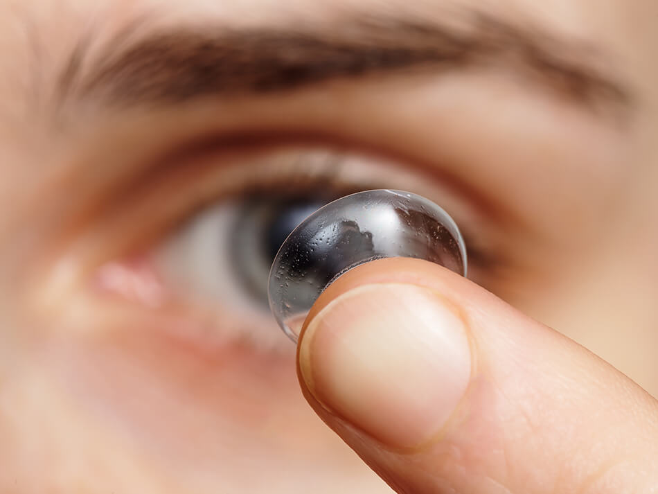 close up of man inserting contact lens in his eye