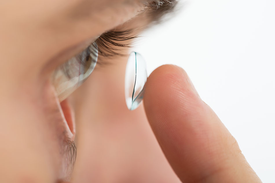 Close-up of a man inserting a contact lens in his eye