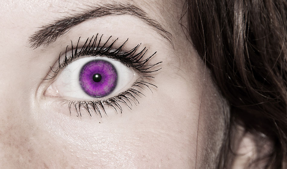 Close-up of woman's eye with purple colored contact lens