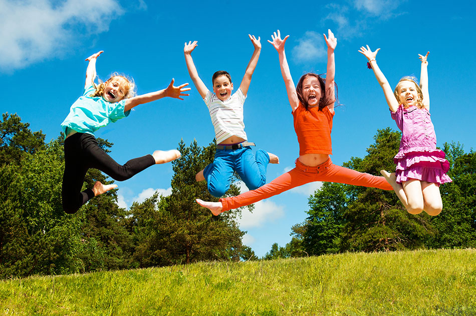 Four children jumping for joy in field