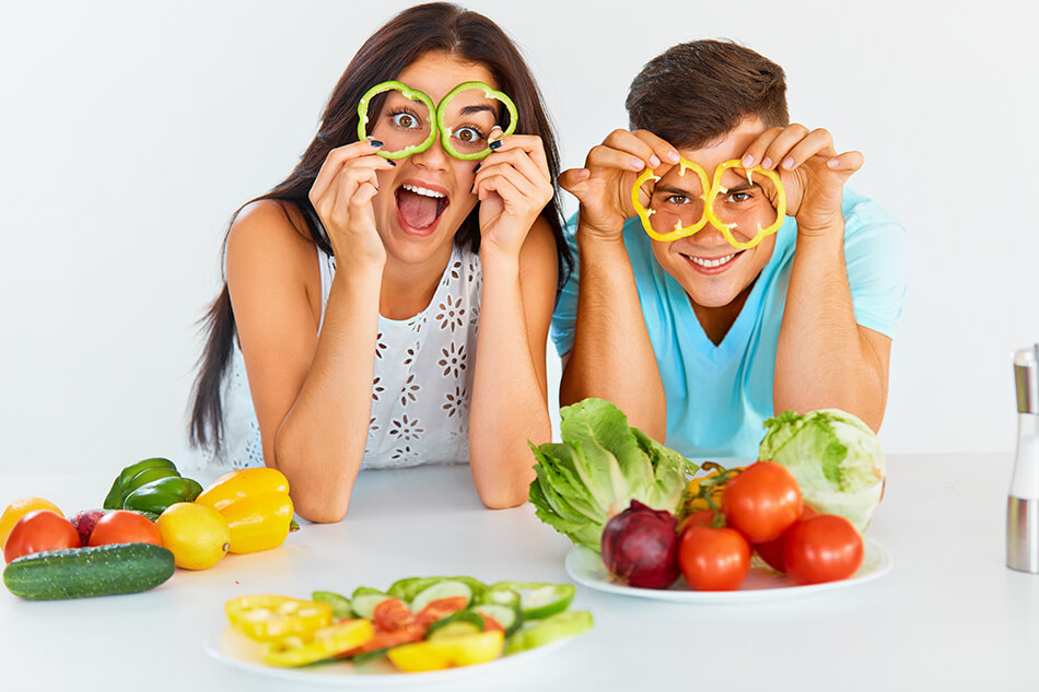 couple with plates of vegetables holding pepper slices up to their eyes