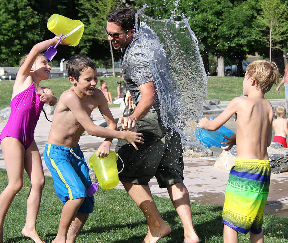 dad and kids enjoy a fun water fight