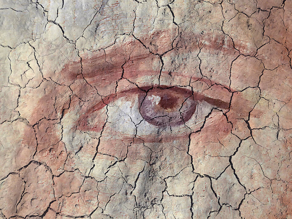 dry cracked earth superimposed over close-up of a human eye