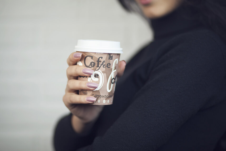 woman with coffee in disposable cup