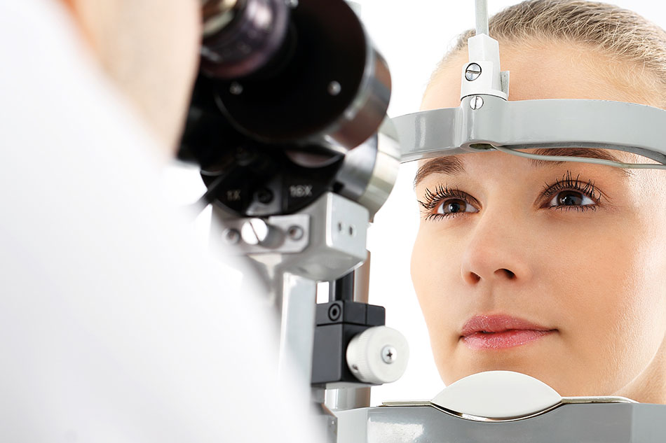 eye doctor looking into woman patient's eyes with a machine