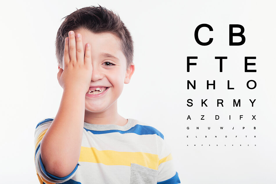 boy covering one eye beside exam chart