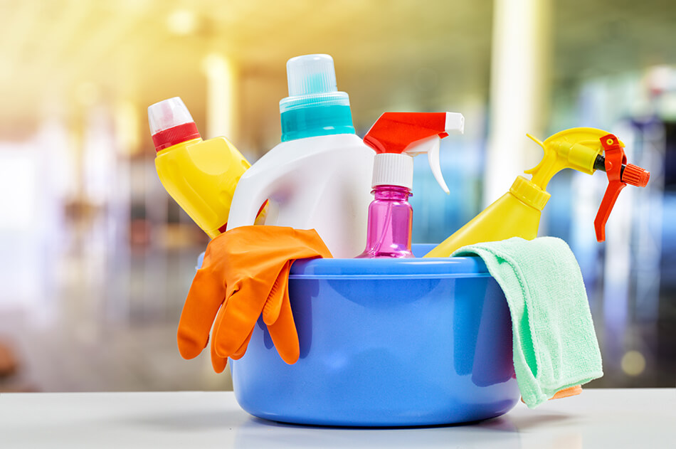 cleaning liquids and gloves in a container