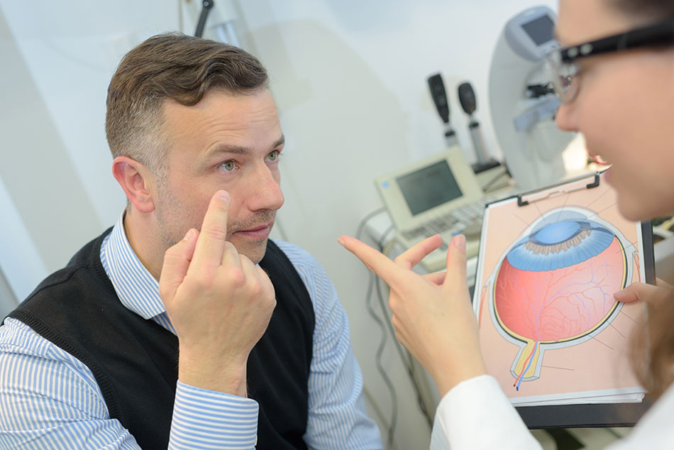 Female eye doctor discussing the shape of the eye with a male patient