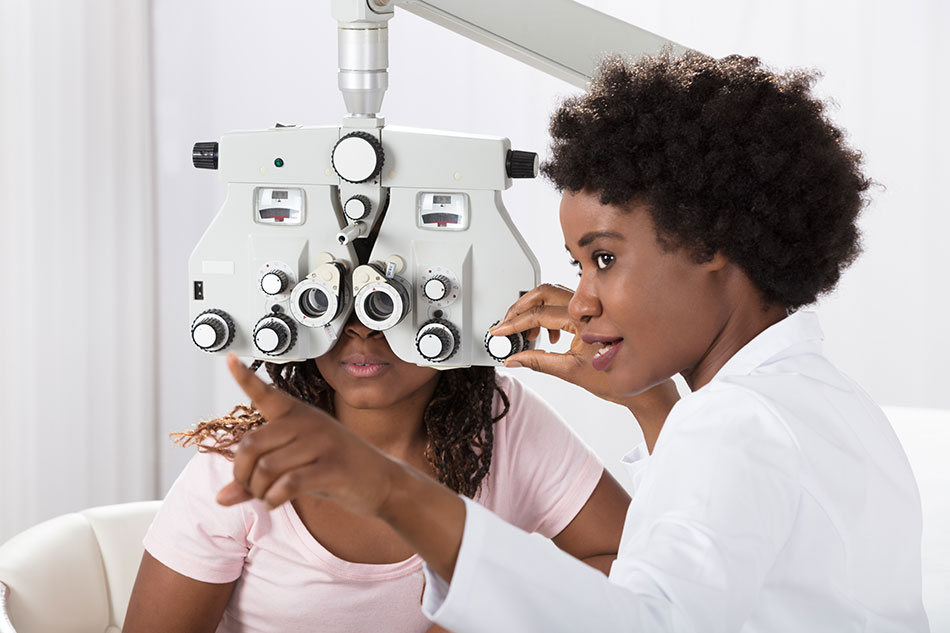 female eye doctor performing eye test on young woman