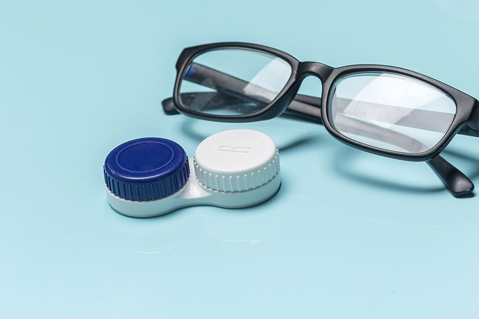 glasses and contact case on light blue background