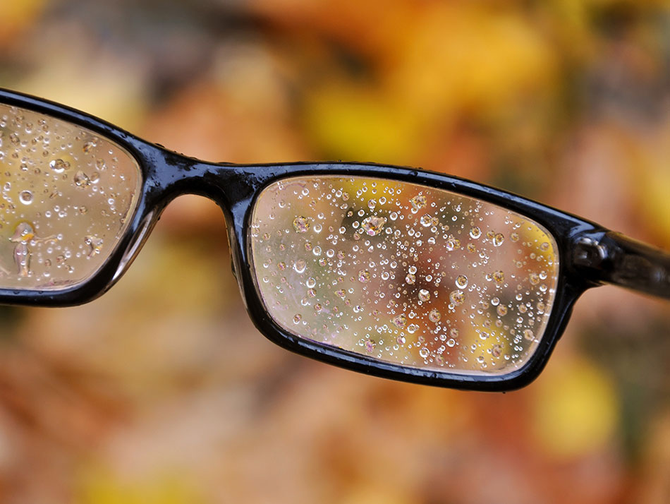 Glasses full of raindrops, leaves in background