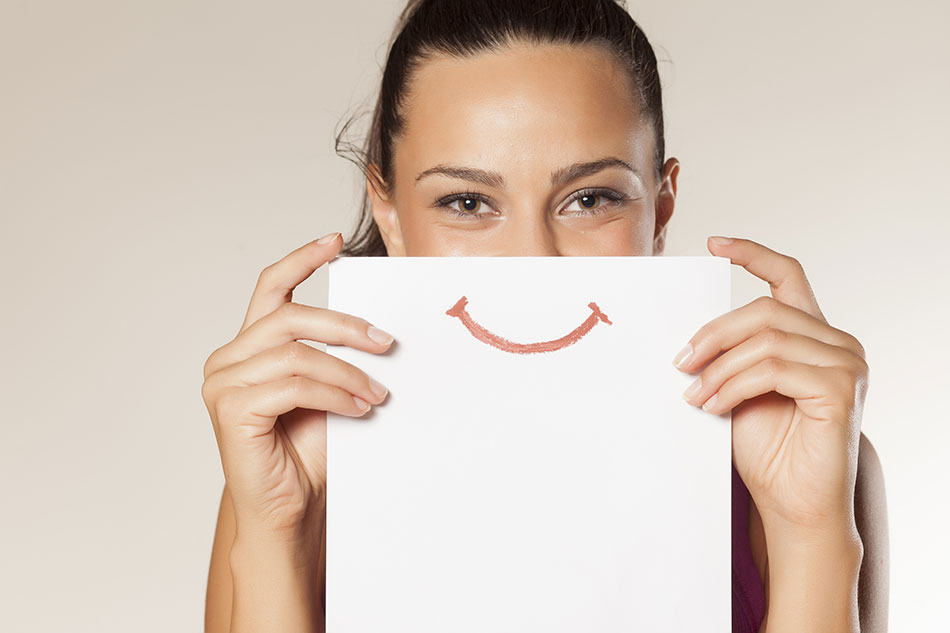 happy woman holding paper with smiley face in front