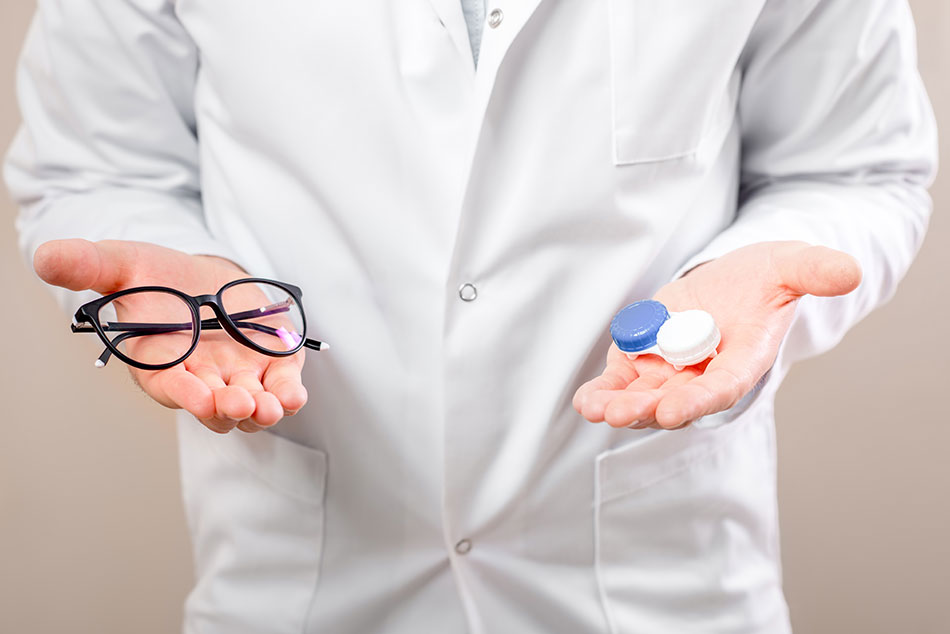 Male eye doctor holding glasses in one hand and contacts case in the other