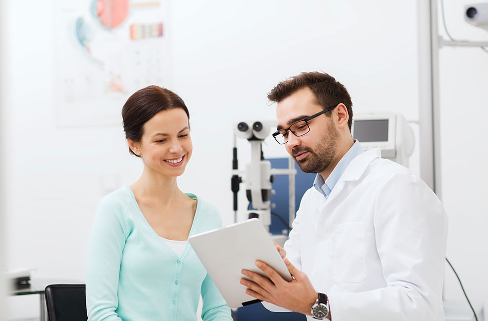 male eye doctor with tablet and female patient