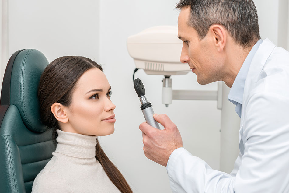 Male ophthalmologist checking female patient's eyes