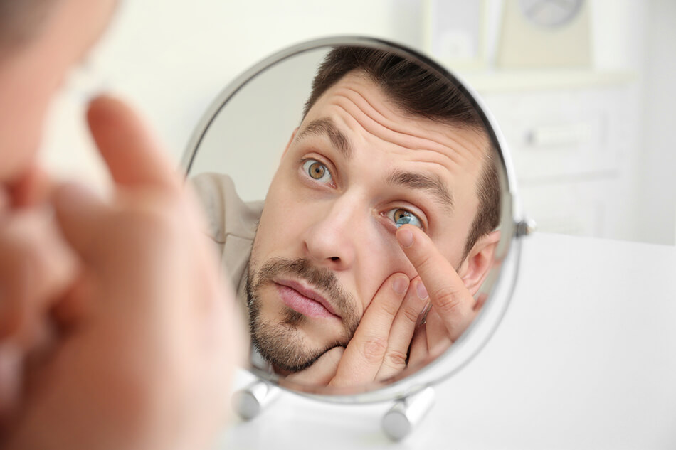 man showing how to put contacts in using mirror