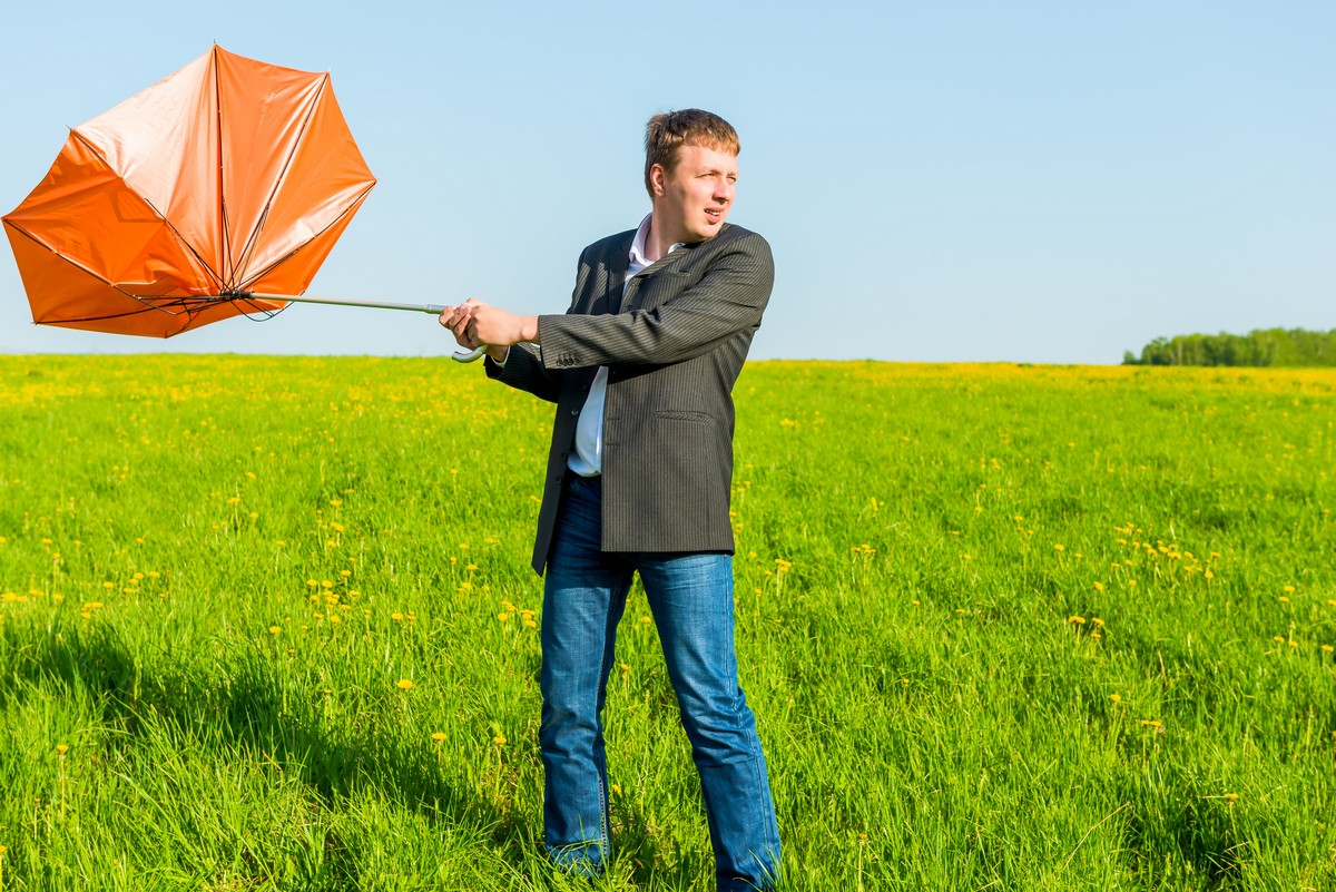 man fighting wind with umbrella blown back