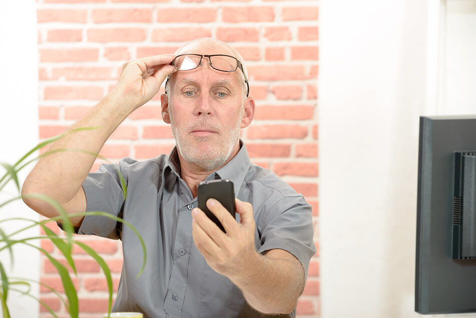 man with mobile phone has trouble reading the screen