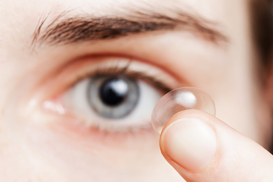 man inserting contact lens into his eye