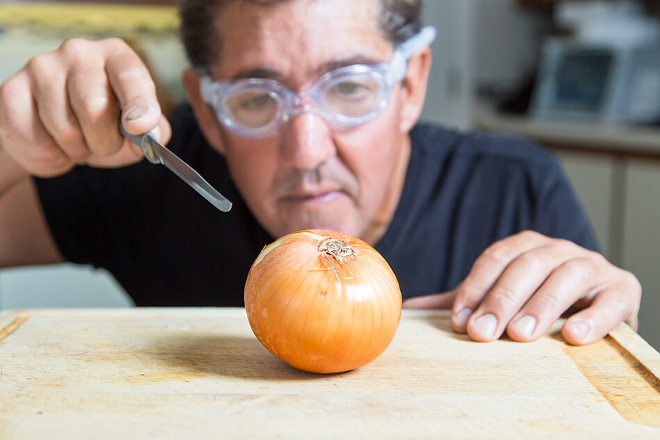 man wearing goggles while cutting an onion for good eye safety in the kitchen