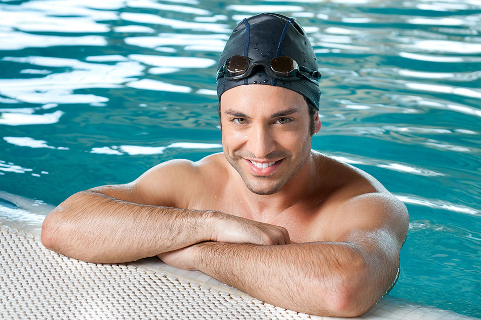 man wearing swimming goggles on his head leaning on side of pool