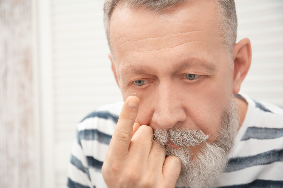 older man putting in contact lenses