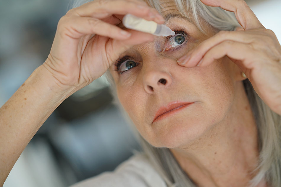 older woman putting drops in left eye
