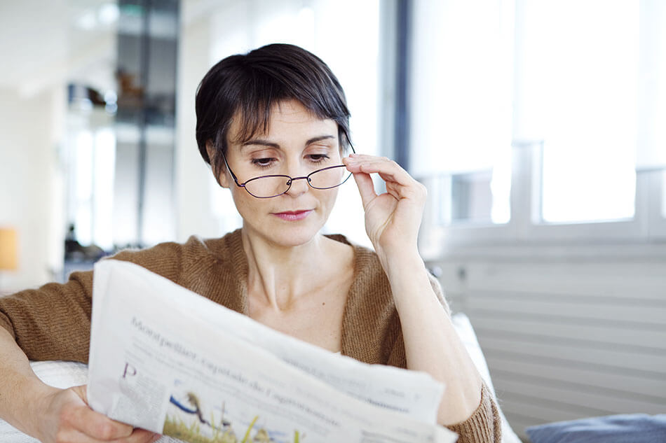 older woman with glasses reading newspaper