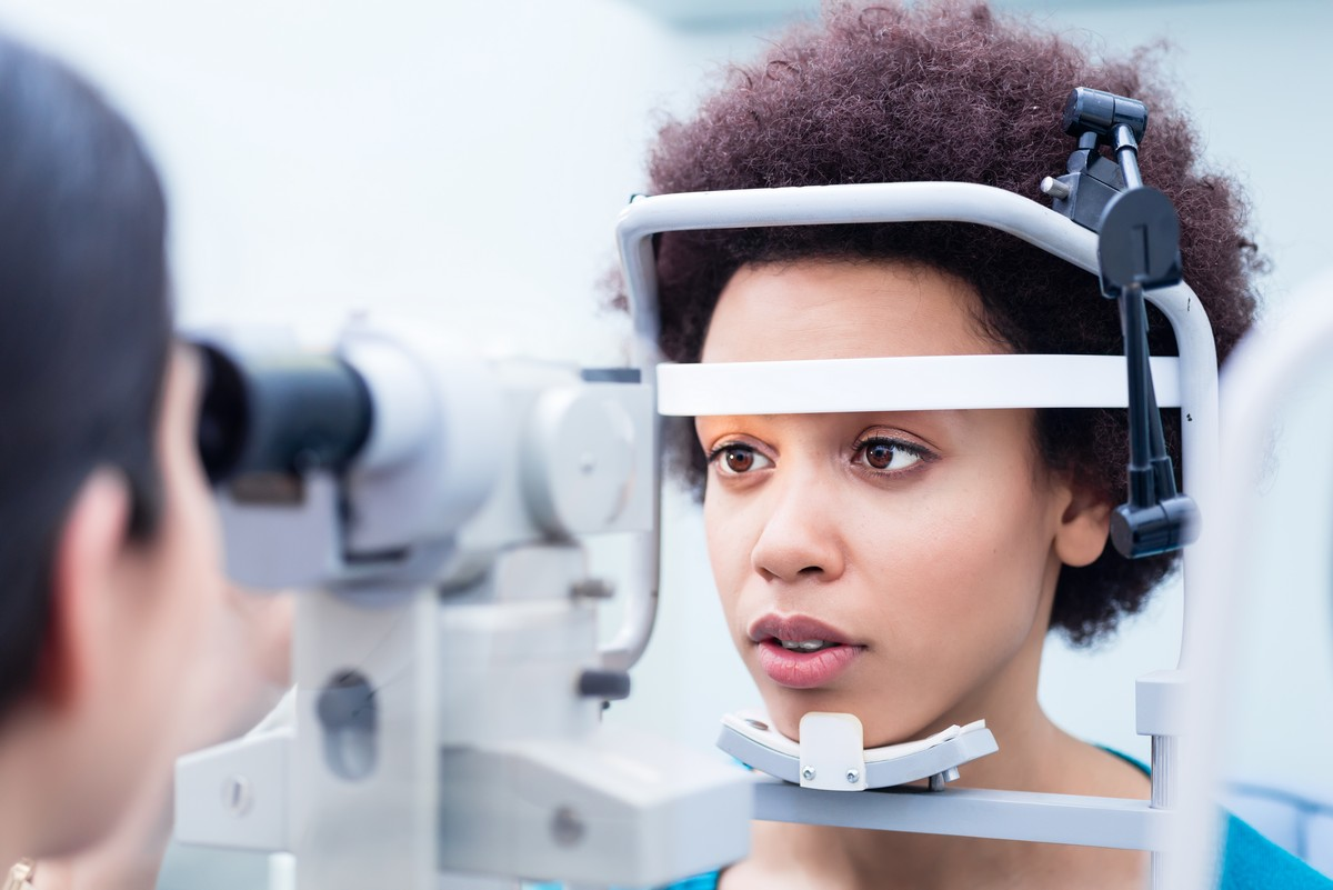 Optometrist measuring young woman's eyes