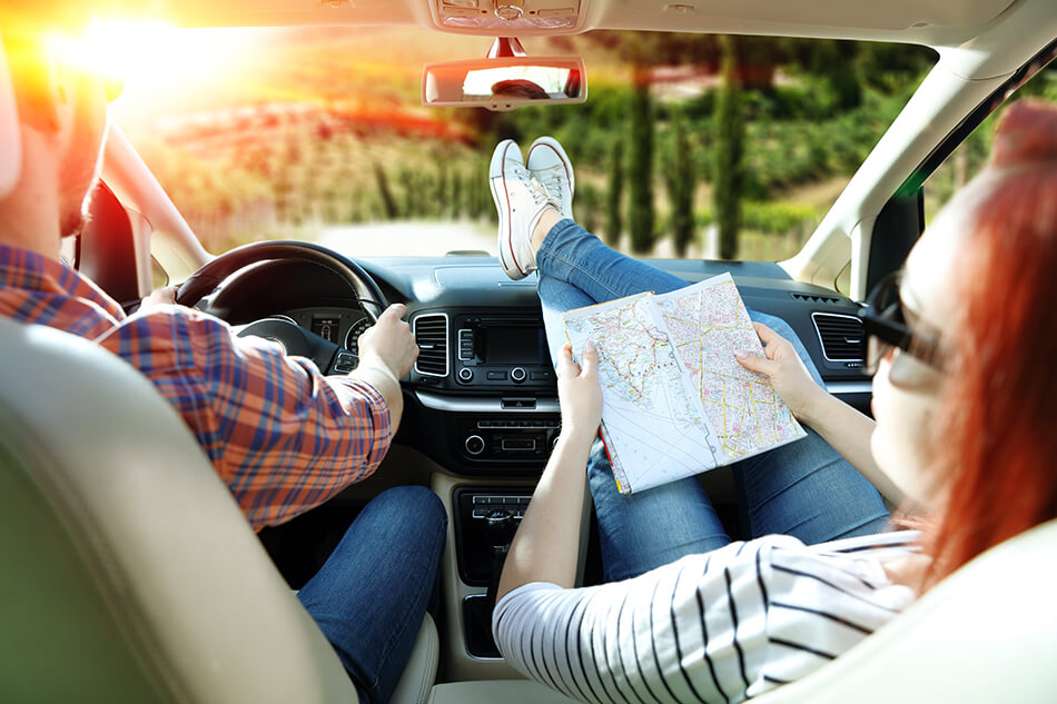 man driving a car while woman is relaxed and looking at road map