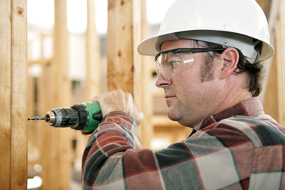 man wearing safety goggles and white helmet while using a drill