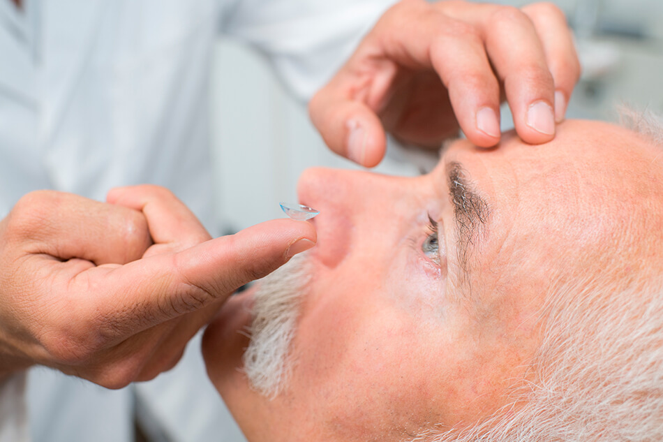 Senior man being taught how to put in contact lenses by a doctor