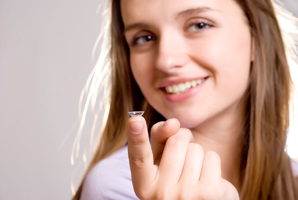 smiling woman showing contact lens on top of index finger