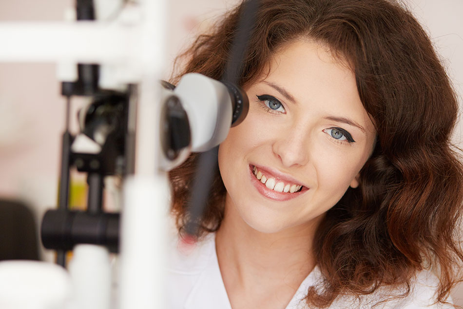 Smiling young female eye doctor in front of eye exam equipment