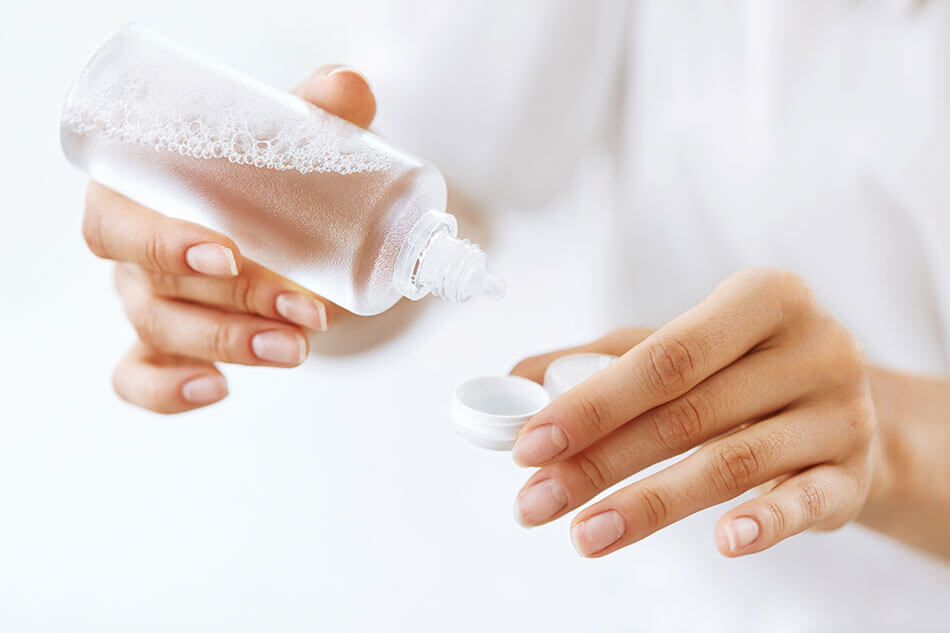woman putting cleaning solution into contact lense case