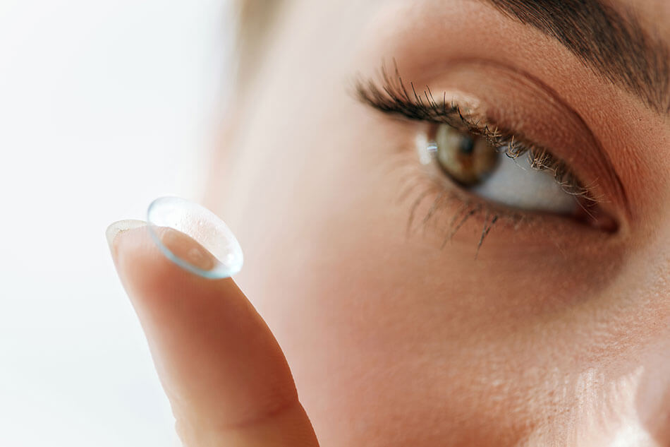 Specialty contact lenses on finger in front of woman's eye