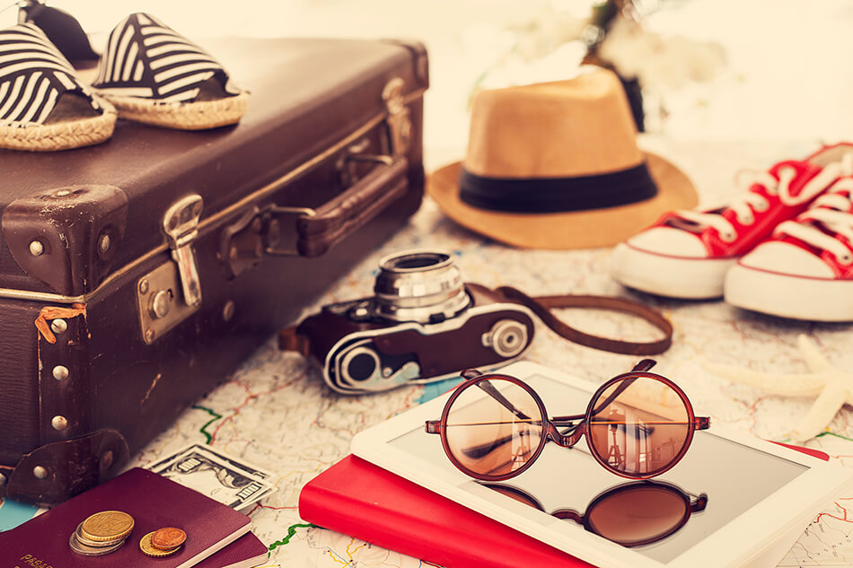 suitcase with camera, sunglasses, money, shoes, and items needed for traveling with contact lenses