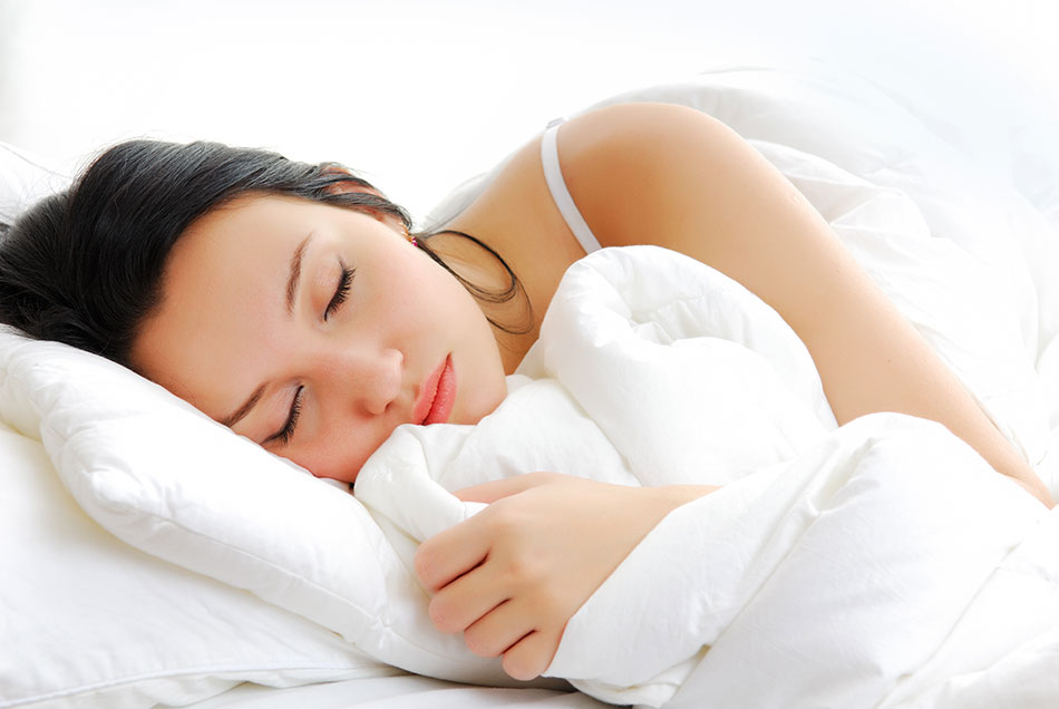 woman asleep in bed with white pillow and blanket
