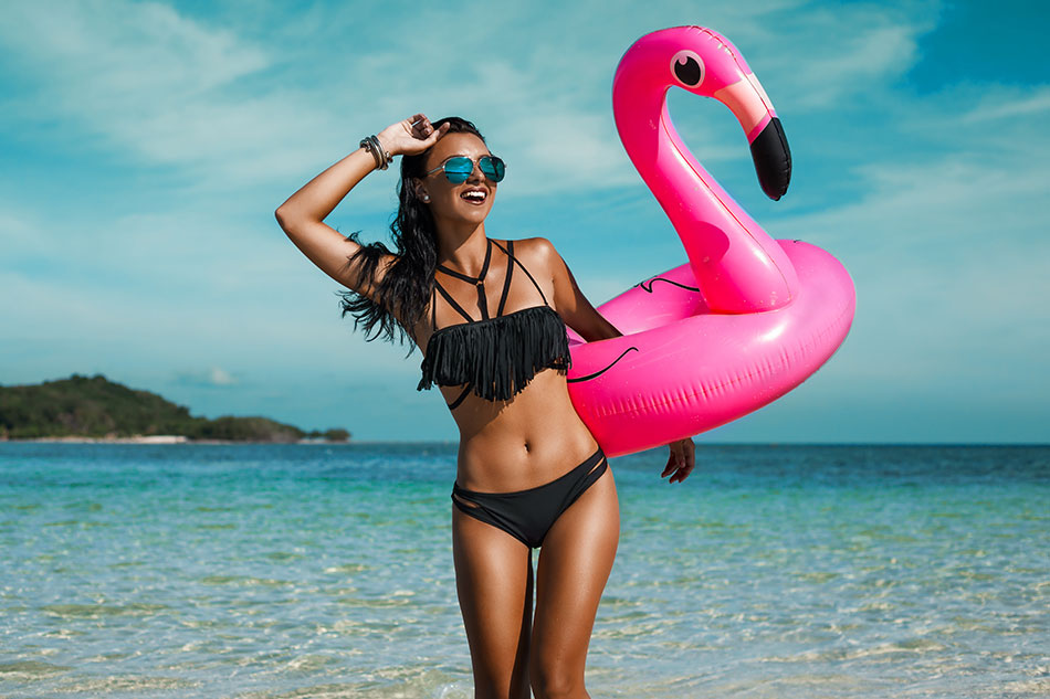 woman in bathing suit on beach with flamingo floating device