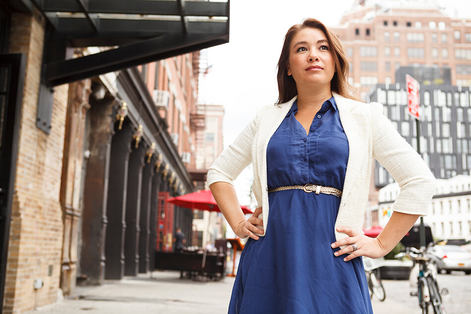 confident woman standing on city sidewalk with hands on hips